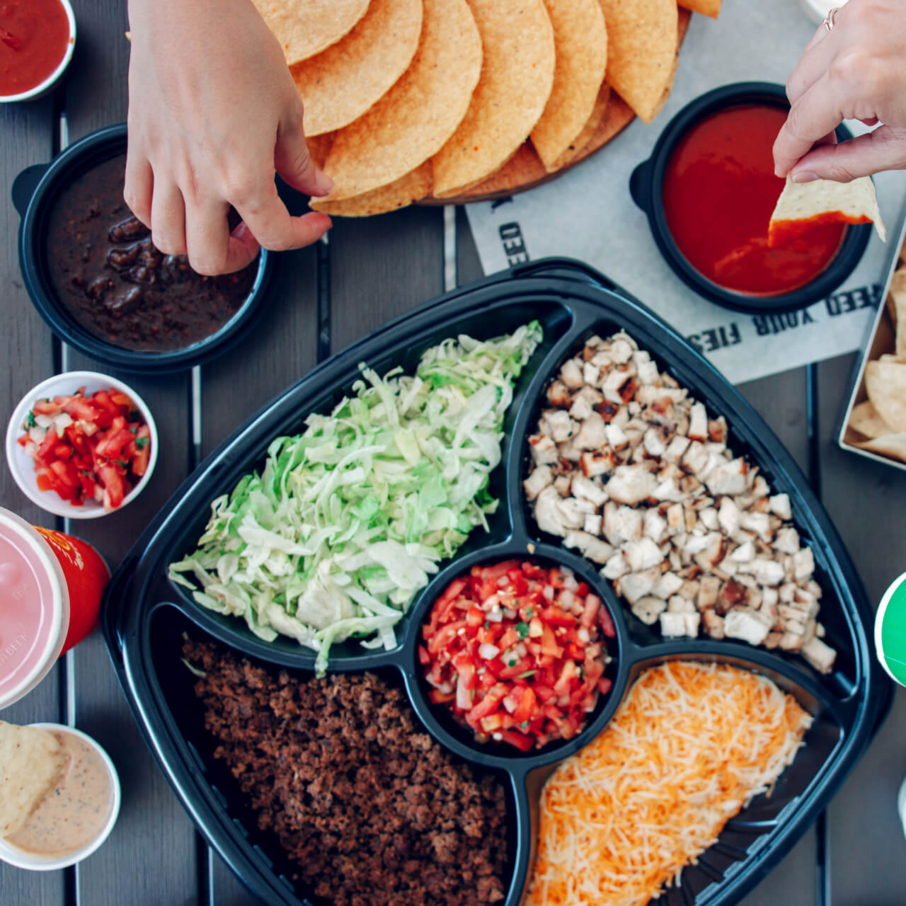 People dipping chips into salsa at a catered event