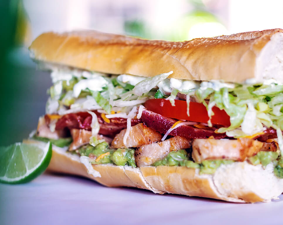 A Mexican-inspired take on a po boy sandwich includes spicy shrimp, cabbage, pineapple, cheese, beans and ranch dressing