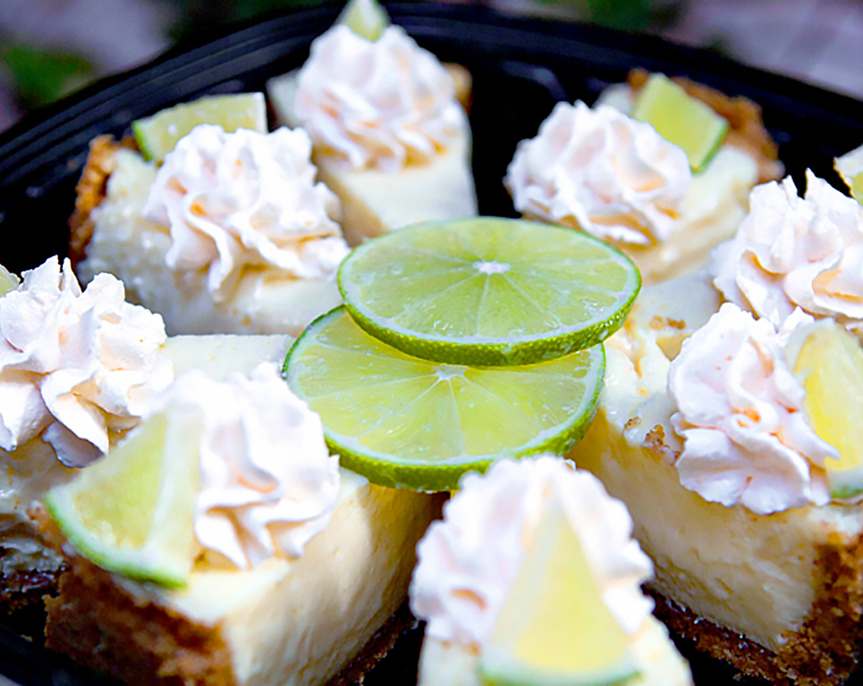 key lime pie topped with whipped cream and a lime slice