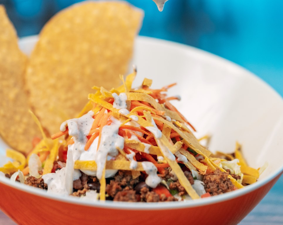 Taco salad in a bowl with tortilla strips and dressing